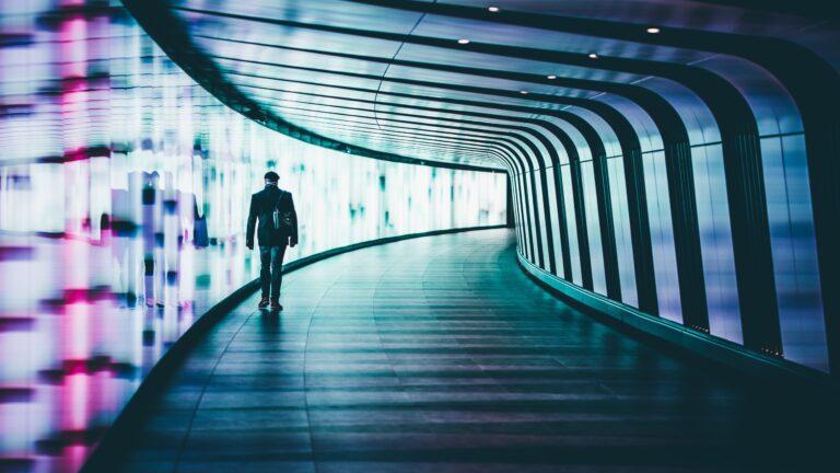 Wandelaar in tunnel met neon verlichting
